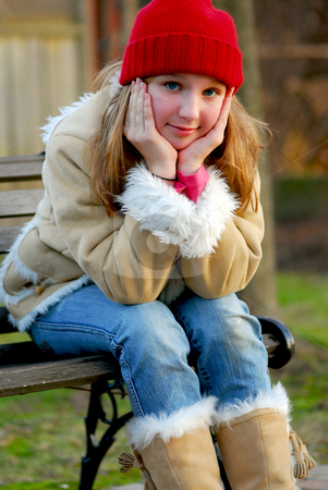 Girl on bench stock photo, Portrait of a young girl sitting on a bench outside by Elena Elisseeva
