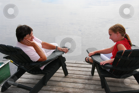 Family on dock stock photo, Grandmother and granddaughter sitting in adirondack chairs on a dock having a conversation by Elena Elisseeva
