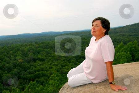 Woman hanging from cliff's edge stock photo, Mature woman sitting on cliff edge enjoying scenery by Elena Elisseeva