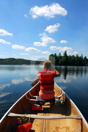 Child in canoe stock photo, Young girl in canoe paddling on a scenic lake by Elena Elisseeva