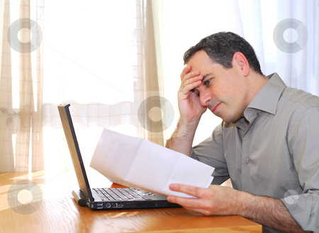 Man with laptop stock photo, Man sitting at his desk with a laptop and bills  looking concerned by Elena Elisseeva