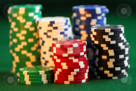 Stacks of chips stock photo, Stacks of gambling chips on green background by Elena Elisseeva
