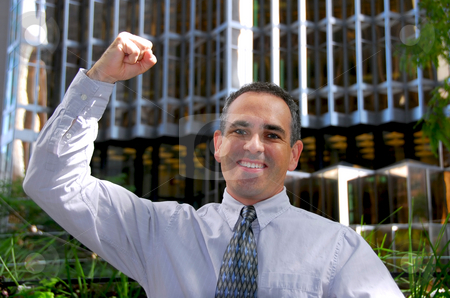 Businessman truimph stock photo, Triumphant businessman in the city raising an arm in victory by Elena Elisseeva