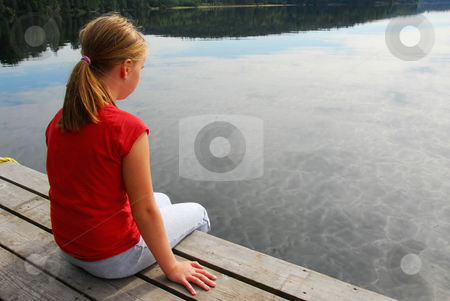 Girl child dock stock photo, Young girl dipping feet in the lake from the edge of a wooden boat dock by Elena Elisseeva