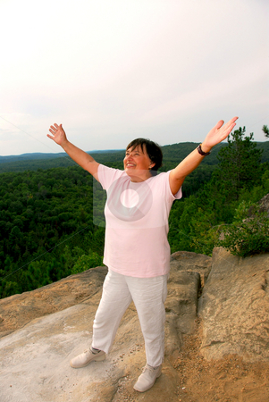 Mature woman cliff stock photo, Mature woman standing on a cliff raising arms in joy by Elena Elisseeva