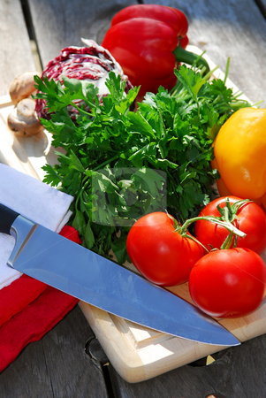 Fresh vegetables stock photo, Assorted fresh vegetables on cutting board on rustic table by Elena Elisseeva