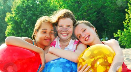 Three girls stock photo, Portrait of three girls on a sandy beach by Elena Elisseeva