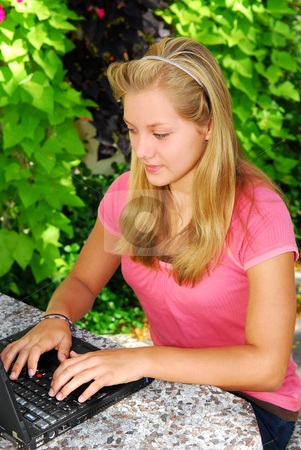Girl with computer stock photo, Teenage girl typing on a portable computer outside by Elena Elisseeva