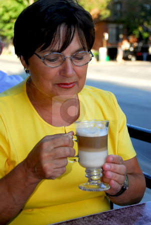 Mature woman coffee stock photo, Mature woman in outdoor cafe holding a coffee by Elena Elisseeva