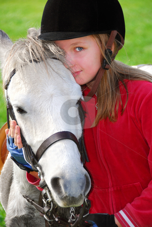 Girl and pony stock photo, Portrait of a young girl with a white pony by Elena Elisseeva