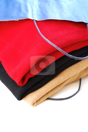 Sweaters stock photo, Folded sweaters in a paper shopping bag on white background by Elena Elisseeva