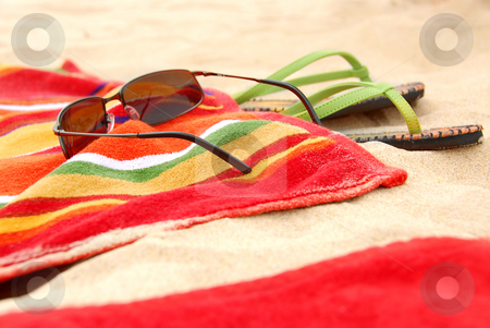Beach items stock photo, Bright colorful towels and other beach items on a beach by Elena Elisseeva