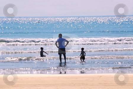 Family beach stock photo, Father and children playing in surf in evening sun by Elena Elisseeva