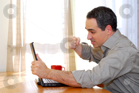 Man with laptop stock photo, Man sitting at a desk punching his computer in frustration by Elena Elisseeva