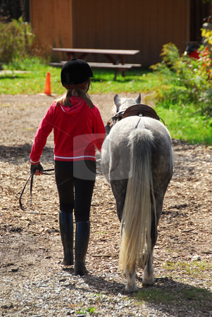 Girl and pony stock photo, Young girl leading her pony back to the stable by Elena Elisseeva