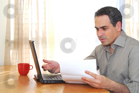 Man with laptop stock photo, Man sitting at his desk with a laptop looking at bills by Elena Elisseeva
