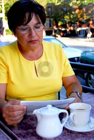Mature woman reading stock photo, Mature woman reading papers in outdoor cafe looking concerned by Elena Elisseeva