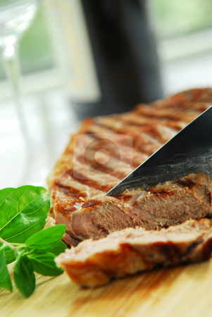 Grilled steak stock photo, Grilled New York steak being cut on a cutting board by Elena Elisseeva