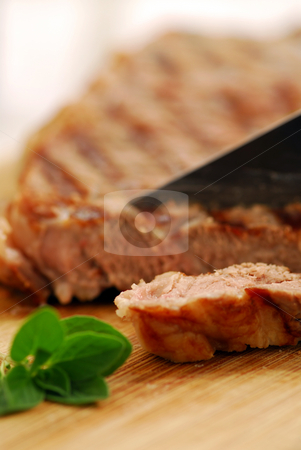 Grilled steak stock photo, Grilled steak being cut on a cutting board, closeup by Elena Elisseeva