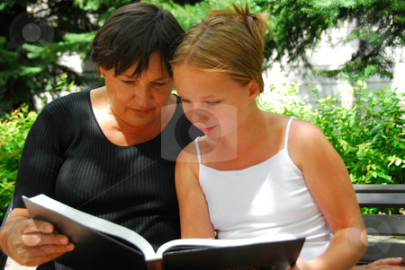Generations book stock photo, Grandmother and granddaughter reading a book by Elena Elisseeva