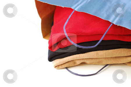 Clothes stock photo, Folded sweaters in a paper shopping bag on white background by Elena Elisseeva