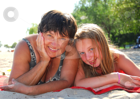 Family beach stock photo, Portrait of grandmother and granddaughter lying on a sandy beach by Elena Elisseeva