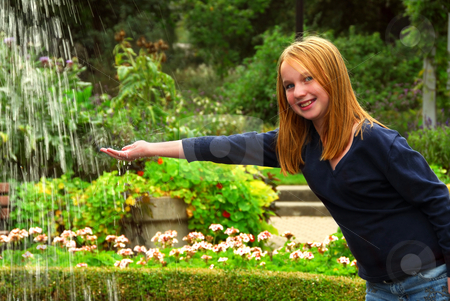 Girl fountain stock photo, Young girl holding her hand under falling water in a garden by Elena Elisseeva
