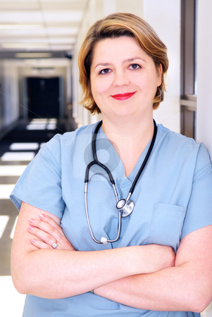 Nurse in a hospital stock photo, Portrait of a smiling nurse in standing in a hospital corridor by Elena Elisseeva
