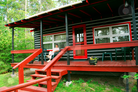 Log cabin woods stock photo, Woman sitting on a deck of log cabin by Elena Elisseeva