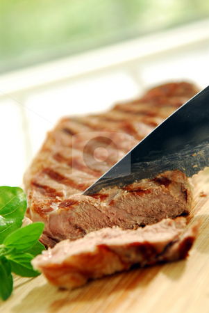 Grilled steak stock photo, Grilled steak being cut on a cutting board by Elena Elisseeva