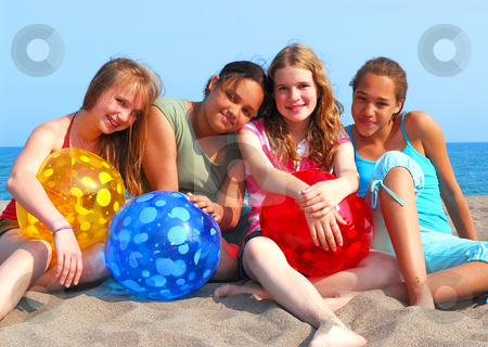 Four girls on a beach stock photo, Portrait of four young girls with colorful beach balls by Elena Elisseeva
