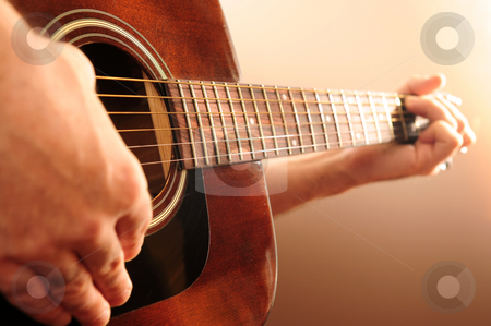 Person playing a guitar stock photo, Hands of a person playing an acoustic guitar by Elena Elisseeva