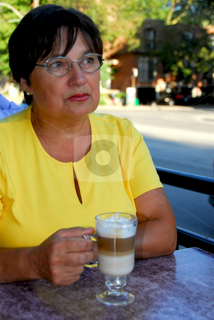 Mature woman coffee stock photo, Mature woman in outdoor cafe with coffee looking sad by Elena Elisseeva