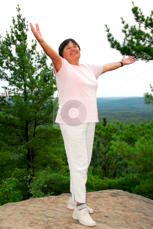Carefree woman stock photo, Mature woman standing on hilltop raising her arms by Elena Elisseeva