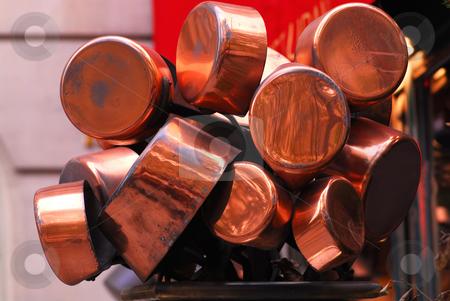 Copper pots stock photo, Bunch of old shiny copper pots near a restaurant by Elena Elisseeva