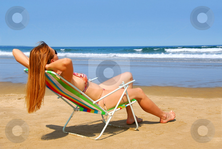 Woman beach stock photo, Young woman relaxing on a beach in a chair by Elena Elisseeva