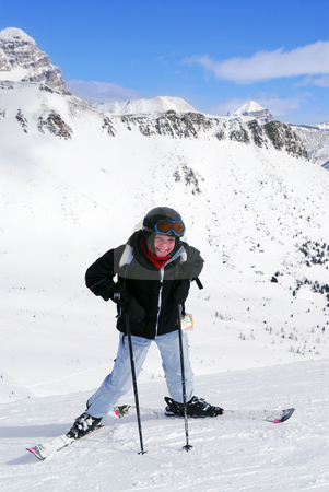 Skiing in mountains stock photo, Young girl downhill skiing on the backdrop of scenic view in Canadian Rocky mountains ski resort by Elena Elisseeva