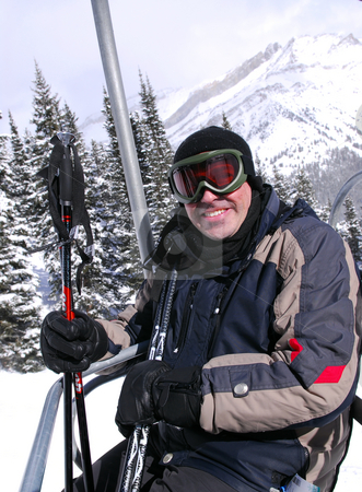 Happy skier stock photo, Happy man on a chairlift at downhill ski resort by Elena Elisseeva