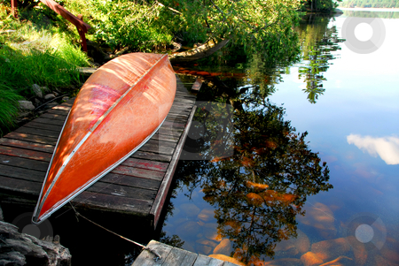 Canoe lake stock photo, Canoe on wooden dock on a lake by Elena Elisseeva