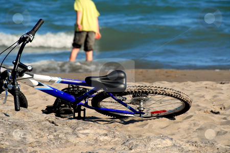 Carefree summer stock photo, Boy walking into water with his bicycle lying on a beach by Elena Elisseeva