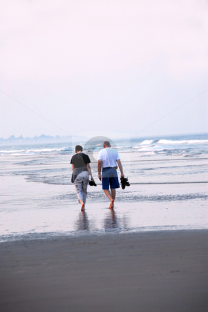 Couple beach stock photo, Mature couple walking on a sandy beach by Elena Elisseeva