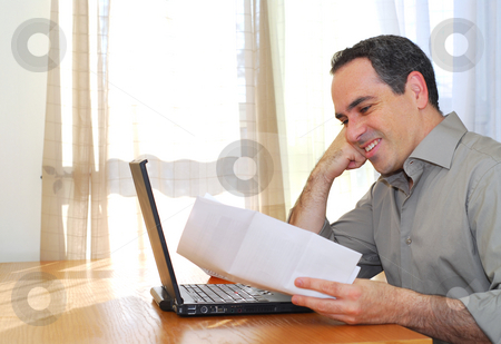 Man with laptop stock photo, Man sitting at his desk with a laptop and papers looking happy by Elena Elisseeva