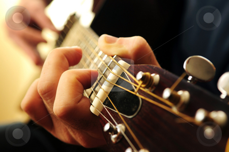 Man playing a guitar stock photo, Hands of a person playing an acoustic guitar close up by Elena Elisseeva