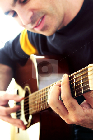 Man playing a guitar stock photo, Man playing a musical instrument accoustic guitar by Elena Elisseeva
