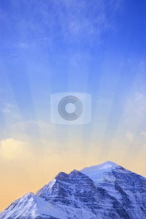 Mountain sunrise stock photo, Sun rising behind a big snowy mountain - background with sun rays by Elena Elisseeva