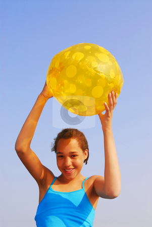 Girl with beach ball stock photo, Pretty young girl holding a yellow beach ball outside by Elena Elisseeva