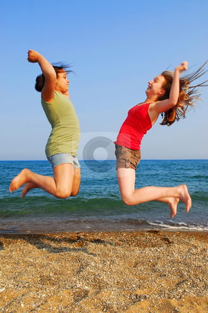 Girls jumping stock photo, Two young girls jumping on a sea shore by Elena Elisseeva
