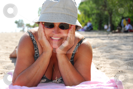 Mature woman beach stock photo, Mature woman in sunglasses lying on a sandy beach by Elena Elisseeva