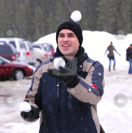 Man juggle snowballs stock photo, Happy man juggling snowballs in winter park by Elena Elisseeva