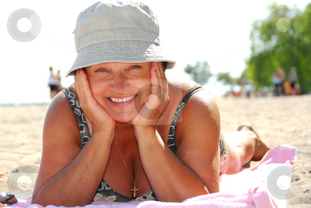 Mature woman beach stock photo, Mature woman lying on a sandy beach by Elena Elisseeva
